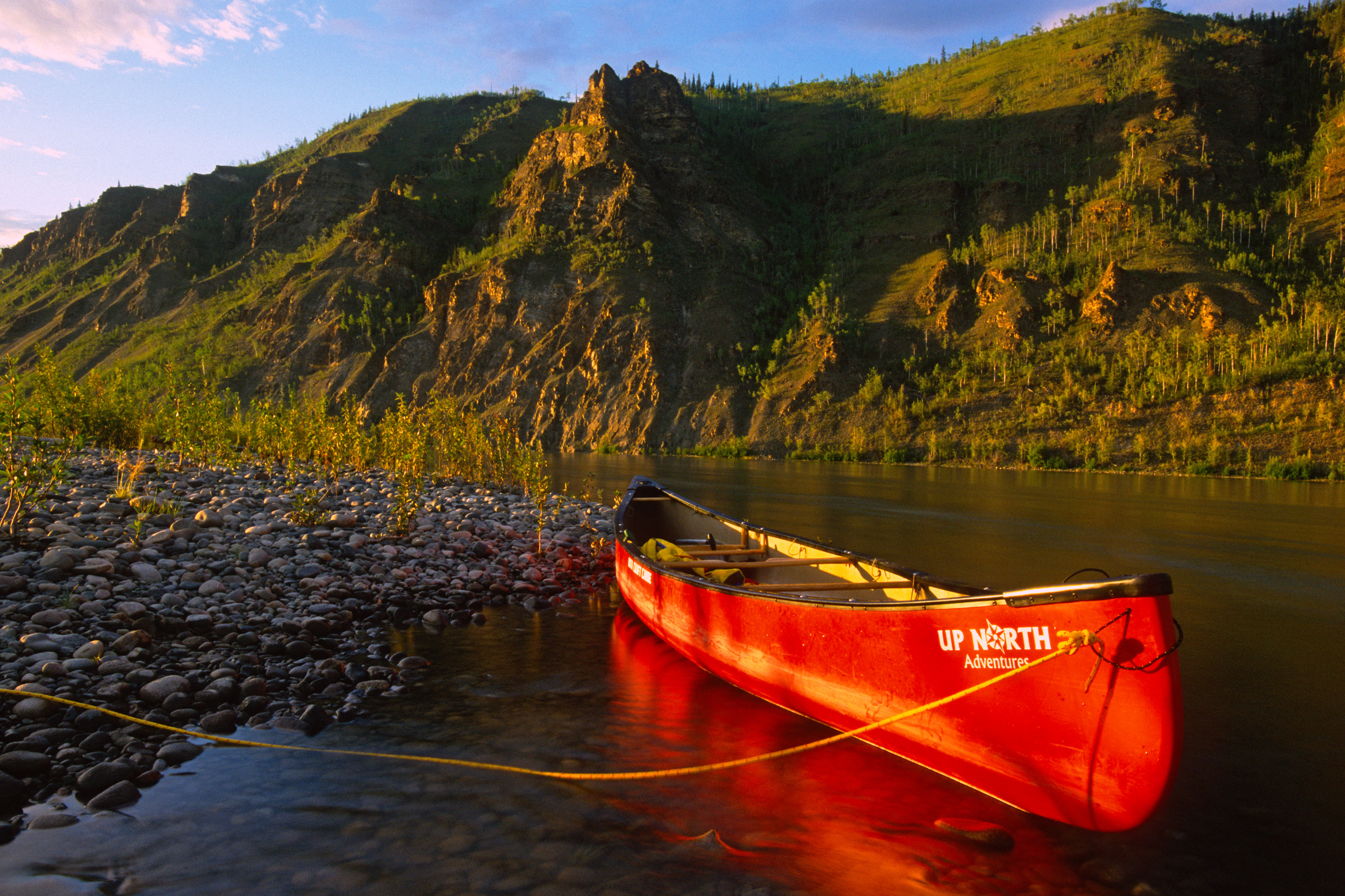 A red canoe beneath cliffs along the Yukon River